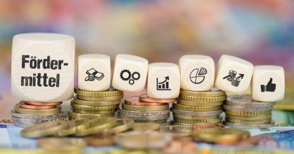 Würfel mit Aufschrift Fördermittel auf Geldmünzen