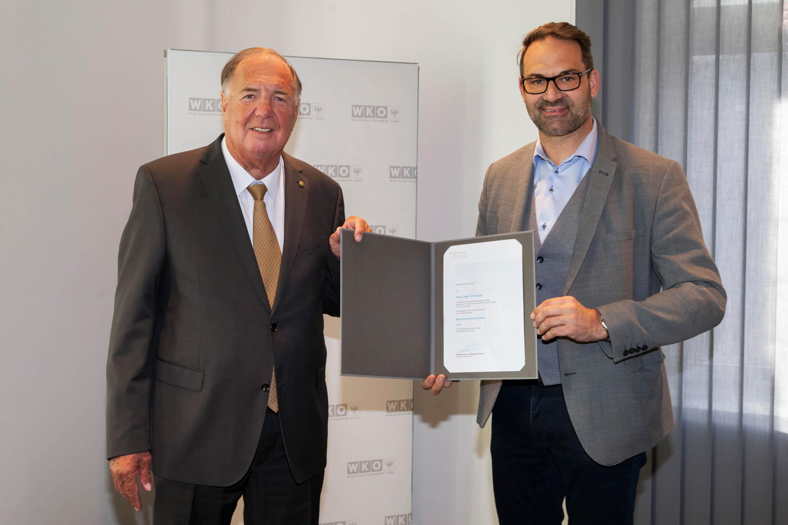 """Sepp Himberger aus Kössen wurde mit dem Berufstitel """"Kommerzialrat"""" geehrt - WK-Präsident Christoph Walser gratulierte (r.)."""