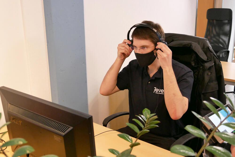Mann vor einem Computer setzt Kopfhörer auf