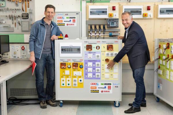 """TFBS-Direktor Martin Gremer (r.) und LIM Helmut Brenner (l.) zeigen sich beeindruckt von den Klemmwägen, die die 2. Klasse """"elevel 2.0"""" geplant und gebaut hat."""