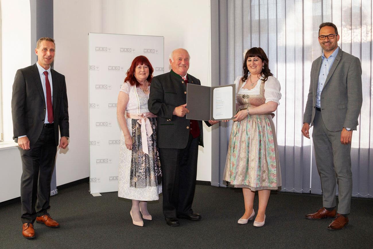 WK-Präsident Christoph Walser (r.) und Spartenobmann Franz Jirka (l.) gratulierten Hans Guggenberger, der die Urkunde im Beisein seiner Frau Olga (l.) und seiner Tochter Angelika entgegennahm.