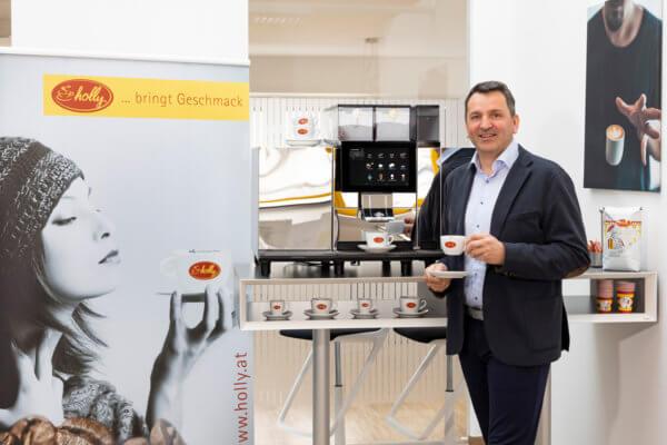 Holly-Geschäftsführer Bernhard Peskoller vor einem Kaffeeautomaten mit Kaffeetasse in der Hand.