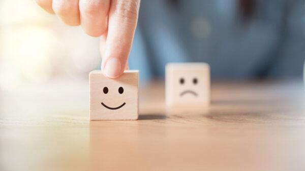 Konsumentenbefragung - Würfel mit positivem Smiley steht im Vordergrund