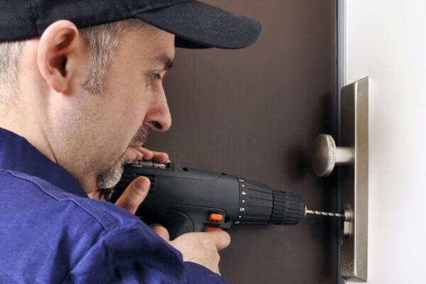 Symbolbild Schlüsseldienste: Mann bohrt Haustürschloss auf