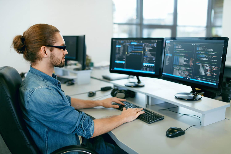 Symbolbild für Informationstechnologie: Mann arbeitet am Computer