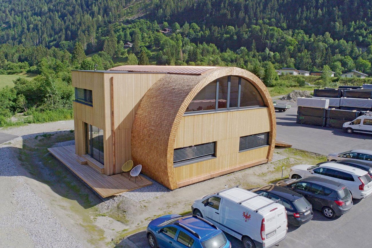 Wie mit Radiusholz auch Gewerbebauten besonders attraktiv gestaltet werden können, zeigt Holzbau Unterrainer sowohl mit seiner Produktions- und Abbundhalle wie auch mit dem neuen Büro- und Verwaltungsgebäude am Firmenstandort Ainet.